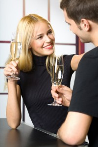 Young happy smiling couple celebrating with champagne