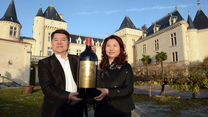Chinese billionaire Lam Kok (L) and his spouse pose for a photograph on December 20, 2013, in front of the Chateau de La Riviere, in La Riviere. The deal which was concluded on December 19 for Chinese billionaire Lam Kok to buy a Bordeaux vineyard, le Château de La Rivière, turned to tragedy today after the helicopter which the billionaire and the vineyard's French former owner James Gregoire were using to fly over the property crashed into the Dordogne river. This photograph was taken less than an hour before the crash. The French former owner of the vineyard James Gregoire, the new Chinese buyer Lam Kok, and Lam Kok's 12-year-old son are still missing. AFP PHOTO / MEHDI FEDOUACH