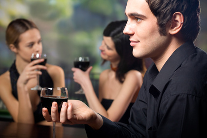 Young man with glass of red-wine and two women