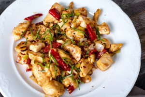 Kung Pao Chicken with Peppers, peanuts and Veggies and sticky glance sauce on wood background