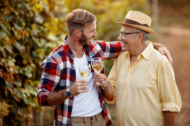 Father and son tasting wine in vineyard.